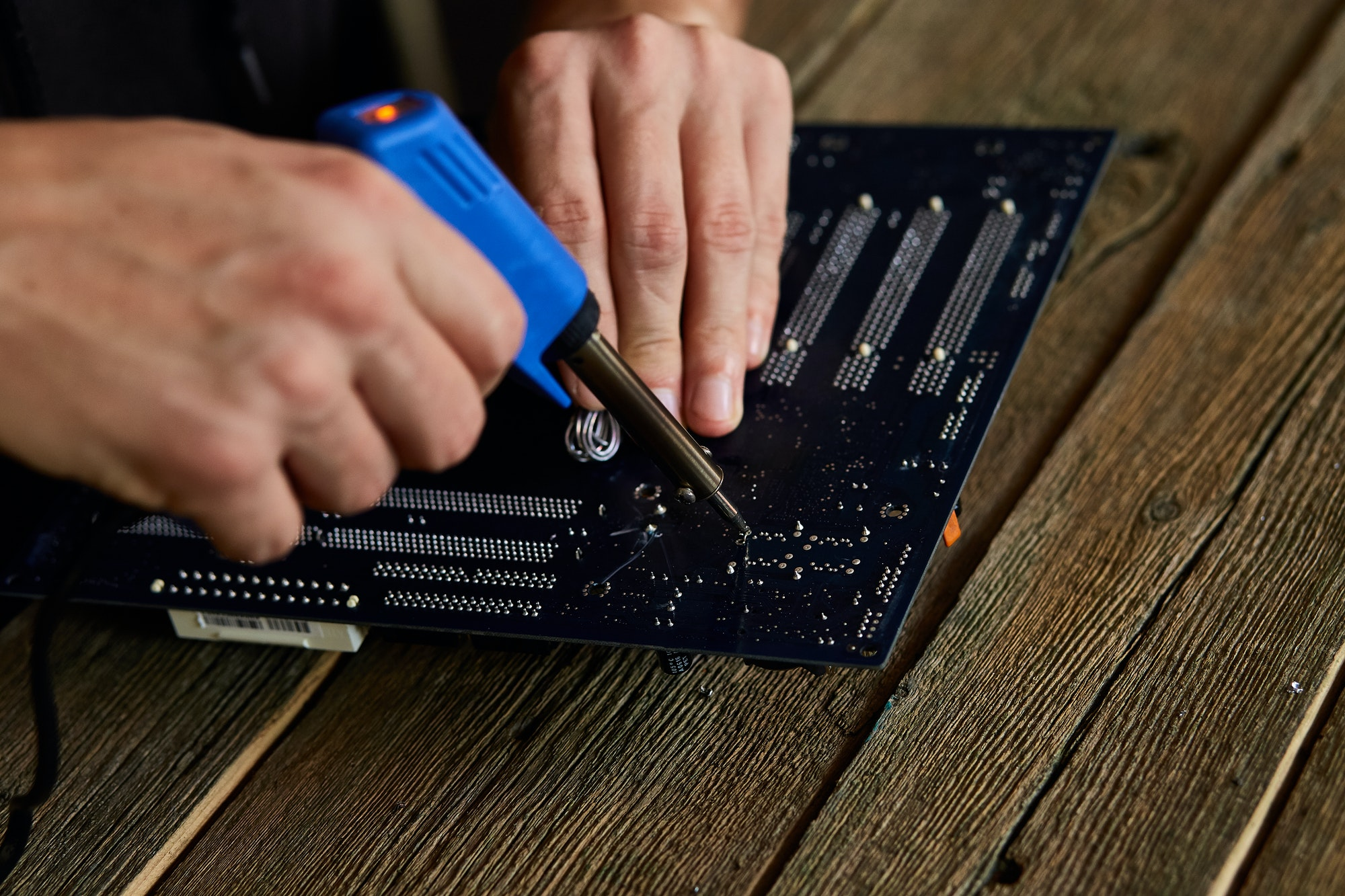 Engineer or technician repair electronic circuit board with soldering iron.